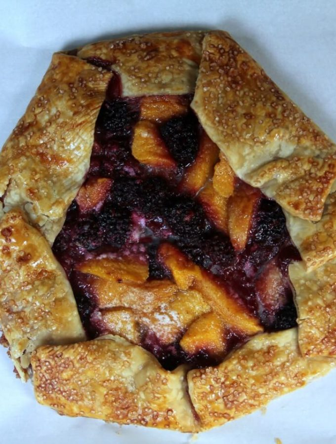An uncut peach and blackberry galette.