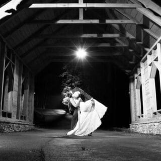 bride and groom under the covered bridge