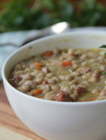 Navy Bean and Ham Soup made easy with canned beans, ham hocks, carrots, celery, dried rosemary and thyme, and a little bacon for flavor. It's the best!