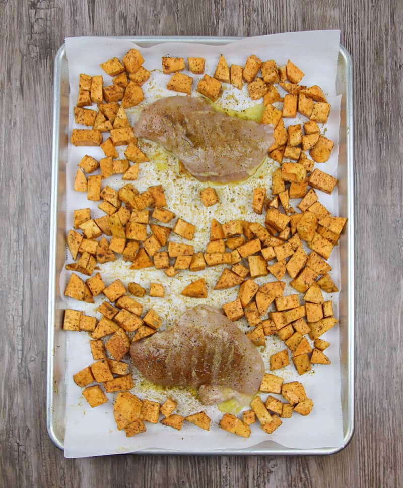 Arugula salad with roasted sweet potatoes, chicken on a baking sheet.